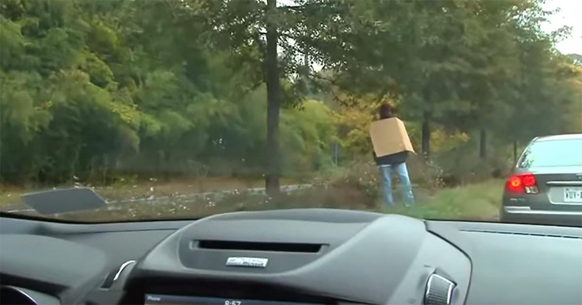 dakloze man met bord langs de weg