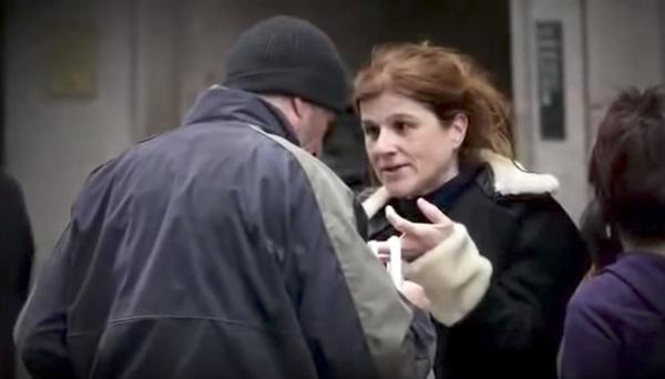 vrouw geeft pizza aan dakloze man