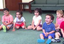Lerares roept haar studenten om in hun handen te klappen, maar let op de kleine jongen in het blauw